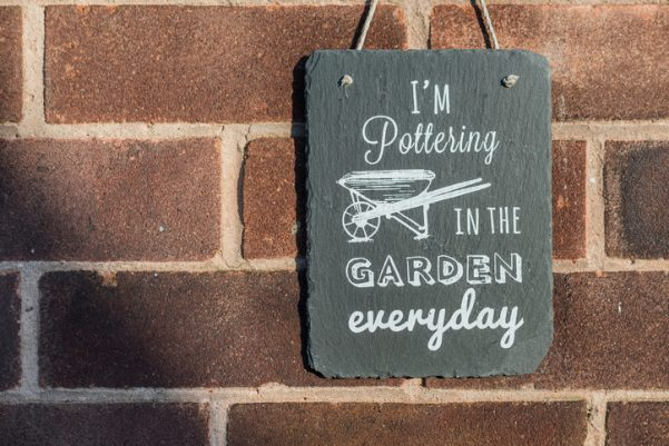I'm pottering in the garden everyday slate garden sign hanging against a brick wall space maximise